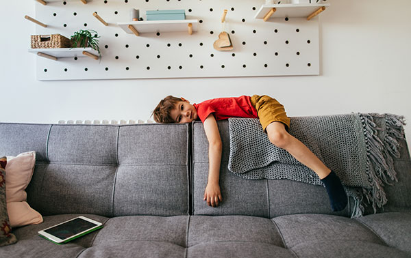child in red shirt lays on the top of a couch looking bored