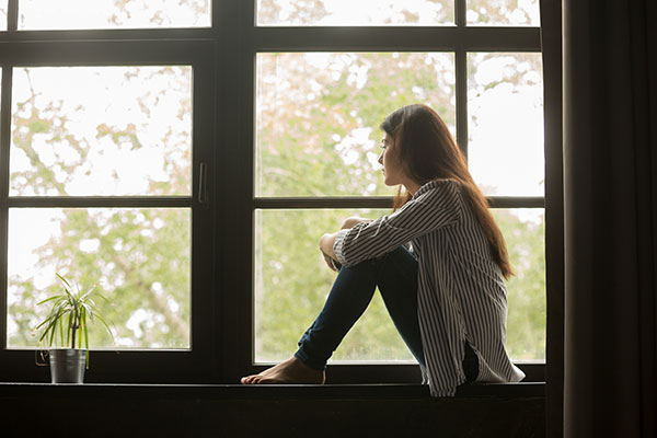 female sitting next to window looking sad