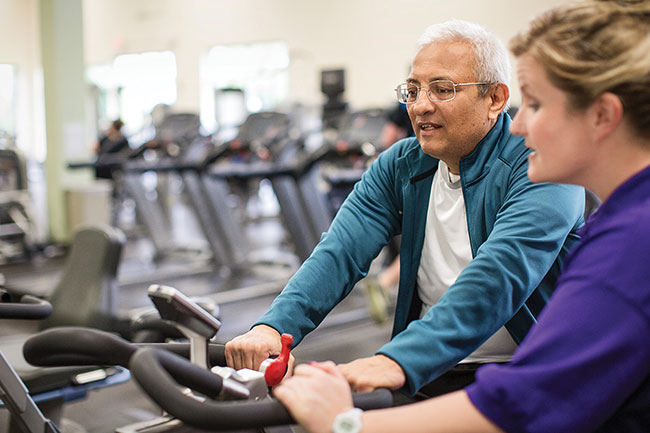 senior working with personal trainer