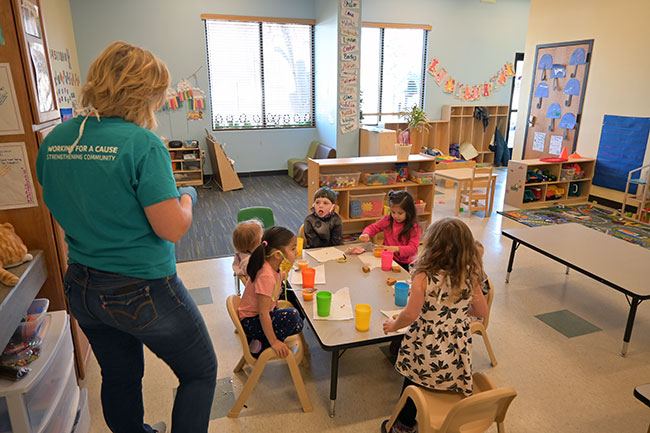 A sunny preschool classroom with children sitting at a table eating snack and a teacher with a mask stands nearby