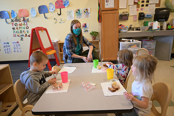 teacher with masks sits with preschoolers