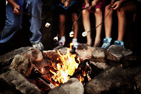 Kids roast marshmallows over a campfire