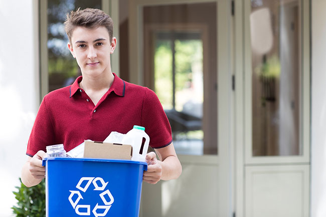 teen boy takes out recycling