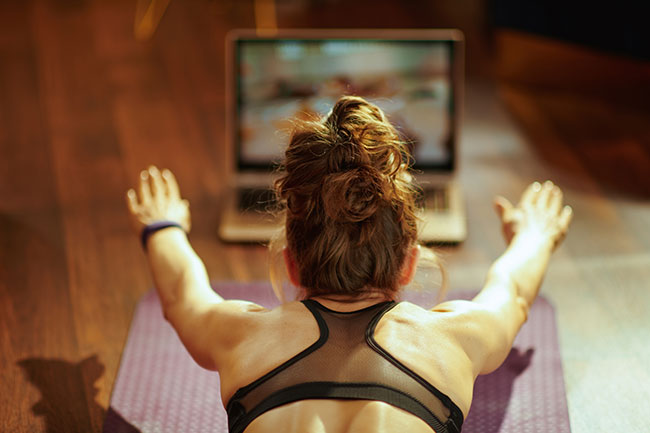 female works out on floor in front of laptop