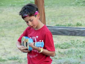 boy playing music at camp