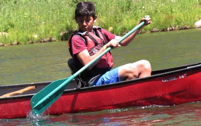 boy in canoe at traditional camp