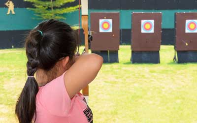 girl doing archery at ymca camp