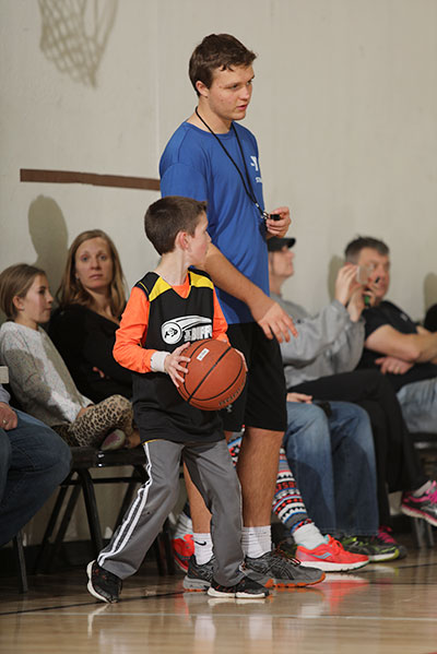 Child and ref interact at a YMCA basketball game
